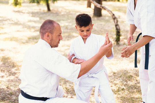 Karate instructor, sensei teaches a child martial arts