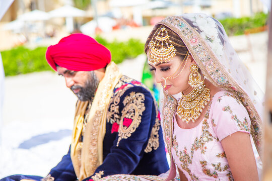 Sikh bride and groom next to each other during marriage ceremony in traditional wedding attire