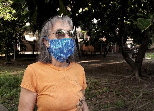Mujer adulta mayor portando mascarilla en un parque, de dia.