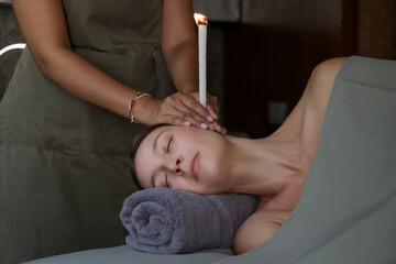 Woman receiving ear candle treatment at spa. Ear coning or thermal-auricular therapy.