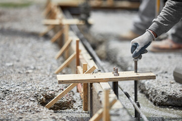 Construction Worker plancing Anchor Bolt into Wet Cement