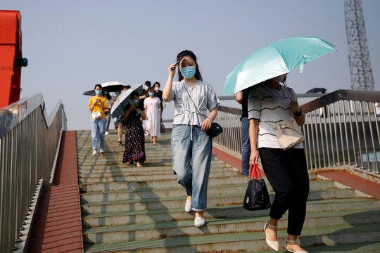 People wearing face masks, following the outbreak of the coronavirus disease (COVID-19), walk on a foot bridge in Beijing
