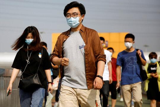 People wearing face masks, following the outbreak of the coronavirus disease (COVID-19), walk on a foot bridge outside a subway station in Beijing