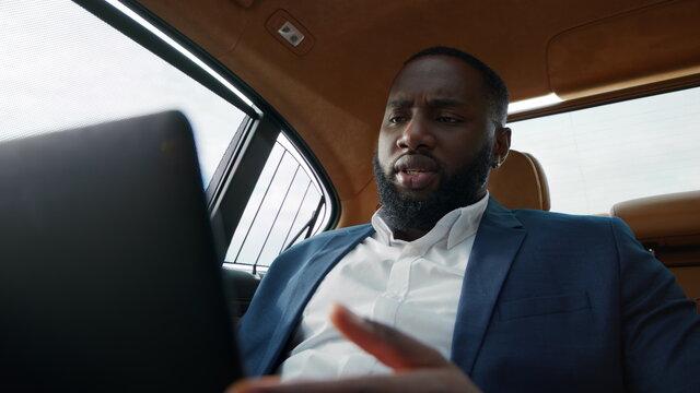 Closeup serious african american man having video call on tablet computer at car