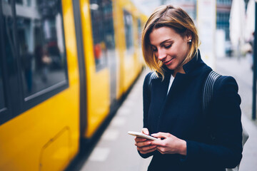 Positive blonde woman holding cellular updating information about city transport on web page,...