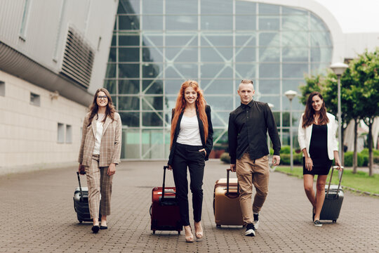 Front view, happy positive young people, three women and a man with luggage outdoor near the airport. Friends returning from a trip. Travel and vacation concept