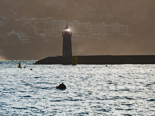 Shinning lighthouse at the end of pier, shaking buoy