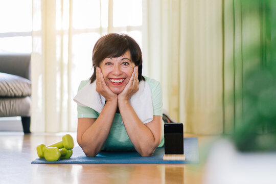 Portrait of a brunette older woman training gym at home.