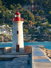 Lighthouse in front of the entrance to the waters of the sea port of Port de Andratx, Majorca island, Spain.