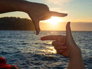 Framing sun above sea. Hands making frame
