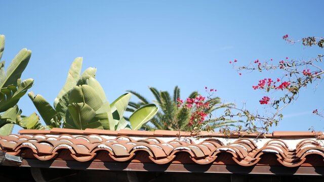 Mexican colonial style suburban, hispanic house exterior, green lush garden, San Diego, California USA. Mediterranean terracotta ceramic clay tile on roof. Rustic spanish tiled rooftop. Rural details