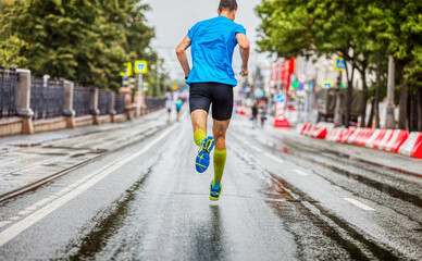 Wall Mural - back man athlete running marathon down street in rainy weather