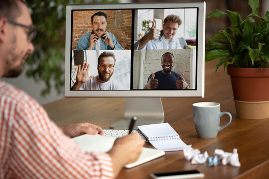 Remote meeting. Man working from home during coronavirus or COVID-19 quarantine, remote office concept. Young businessman, manager in front of monitor during online conference with colleagues and team