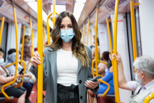 Enterprising young woman wearing a face mask travelling on public transport during rush hour. Selective focus. New normal concept.