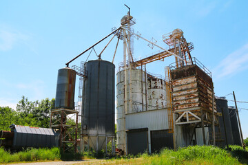large farming community co-op agricultural feed grain and corn silo and elevator building against a blue sky in rural america perfect for industry farming and commercial agriculture marketing