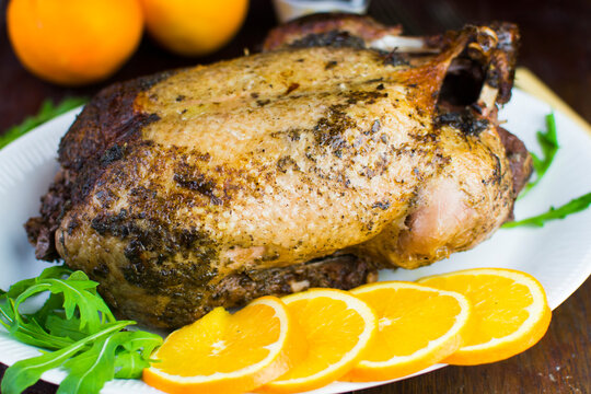 Festive roast duck on wooden table with oranges, hoi sin sauce and arugula leaves.
