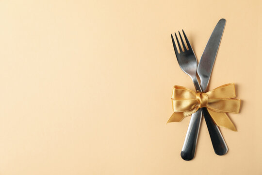 Cutlery with bow on beige background, space for text