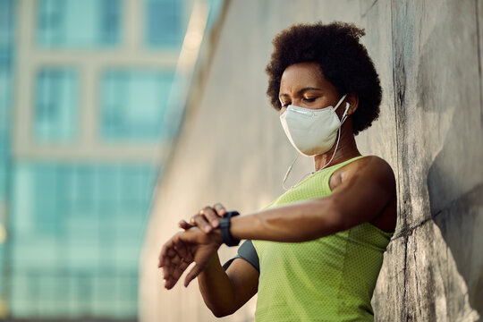 African American female runner with face mask using fitness tracker outdoors.