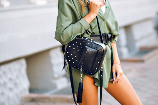Close up fashion details of woman holding trendy black backpack, wearing mini green dress, minimalistic casual modern style.