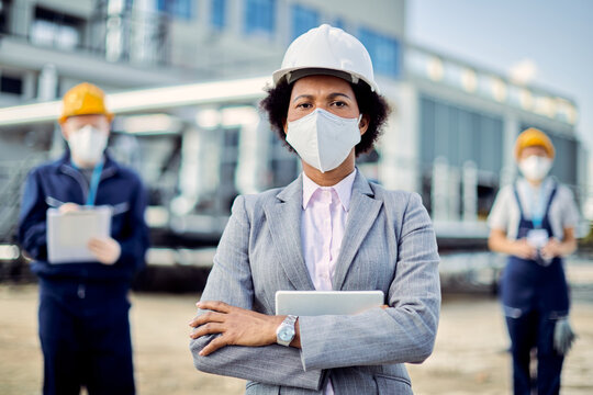Black confident businesswoman standing with crossed arms while wearing face mask at construction site.