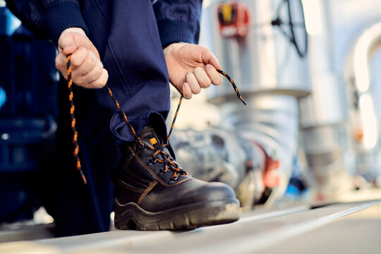 Unrecognizable manual worker typing shoelace at construction site.