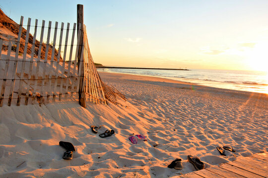 Summertime on Cape Cod, Massachusetts. Long shadows and warm late afternoon sunlight illuminate this typical Cape Cod beach scene with abandoned footwear left by beachgoers.