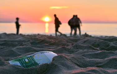 Two guys, a man and a boy looking for a lost 100 euro banknote against the background of a sea sunset