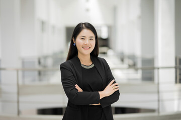 Portrait of a cheerful middle-age businesswoman in business suit stands in the company building with confidence arms crossed. Modern business woman in the office with copy space. Business stock photo.