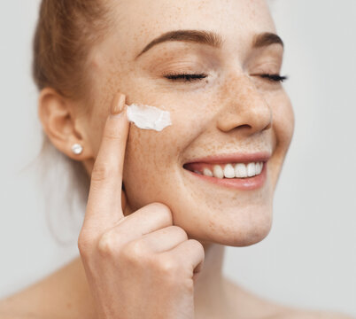 Freckled caucasian ginger lady applying on face anti aging cream and smile on a white studio wall