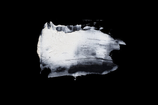 Brushstroke with a thick white paint, isolated on a black background.