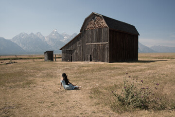 Girl in blue dress sitting near barn on Mormon Row  Grand Tetons seen from back