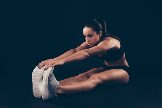 Profile side view of her she nice-looking attractive sportive purposeful focused strong muscular lady working out leaning body sculpt warming limbering up isolated over black background