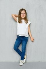 Little girl in blouse and jeans leaning to the wall in studio