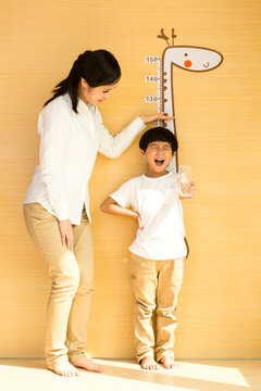 Young mother measuring height for son at home