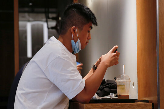 A man lowers his surgical mask at a restaurant following the coronavirus disease (COVID-19) outbreak in Hong Kong
