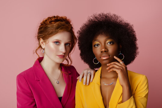 Diverse beauty, fashion: studio portrait of two beautiful confident multiethnic women wearing colorful blazers, jewelry, posing on pink background. Different nation, multiracial friends concept.