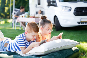 Children with mobile phone on camping holiday