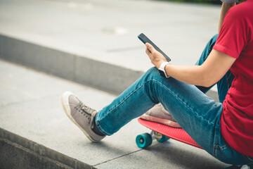 Asian woman sit on skateboard using smartphone in modern city