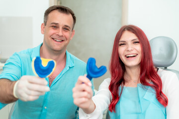 Happy doctor dentist with his patient show the result of impressions of her teeth on a spoon with silicone material
