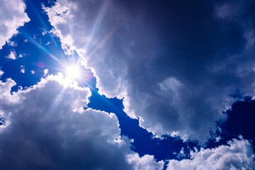 The sun rises between divine-inspired bluish storm clouds.