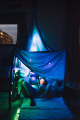 Two children read a digital story on a tablet hidden under a sheet-built fort in their living room before bed.