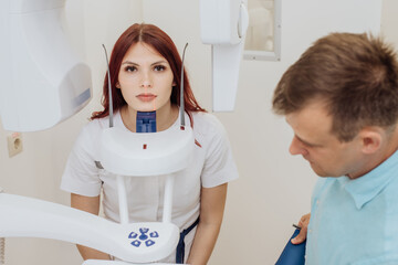 A girl patient makes a panoramic X-ray of the oral cavity on an orthopantomographic apparatus, and the dentist takes a picture