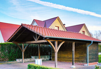 Fototapeta Wooden carport with red brick roof on a new house. obraz
