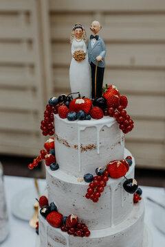 Sommerliche Hochzeitstorte mit Beeren und altem Brautpaar als Figur