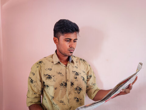 Young South Indian clean shaved guy in green shirt reading newspaper. Isolated on pink background. Daylight