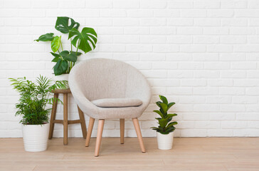 Elegant armchair and green plants on white brick wall background