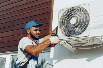 Photo sur Toile Les Textures Repairman in uniform installing the outside unit of air conditioner