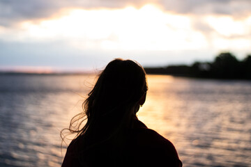 Silhouette of a girl at sunset on the lake. Girl watching the sunset over the lake