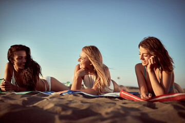 group of three young females laying down on the beach, talking, smiling, enjoying the sunset