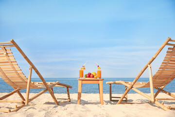 Wooden deck chairs near table with fruits and drinks on beach